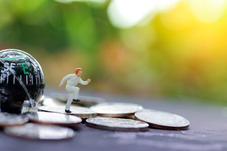 Miniature businessman running on coins stack and compass, Business concepts.  Stock Photo