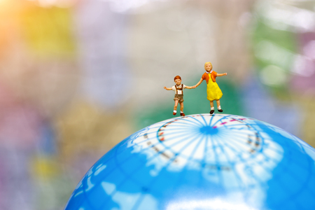 Miniature people, children with brother standing on globe.  Stock Photo