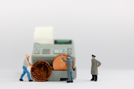 Miniature workers rolling coin to the cash machine , financial,retail,marketing and business concept. Banque d'images
