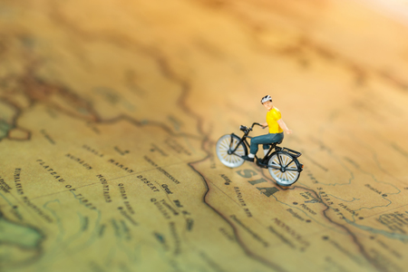 Miniature people  cycling on the map on map, travel or business concept.