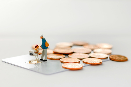 Miniature people : Father and children go shopping / buying with cart on credit card and coins. Concept of tourism, shopping or business. Reklamní fotografie