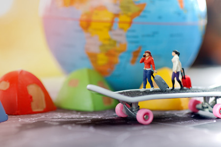 Travel around the world and the adventure. Miniature people with baggage walking on skateboard with globe and tent bed.