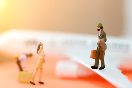 Traveling or business trip concepts. Miniature business people with baggage standing on airplane.  Stock Photo