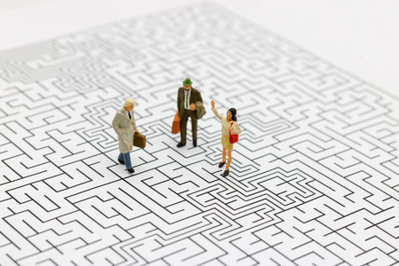 Miniature people: Business team standing on center of maze. Concepts of finding a solution, problem solving and challenge. Stock Photo