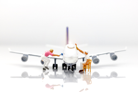 Miniature people: Workers  team brush painting airplane. Concept maintenance of aircraft