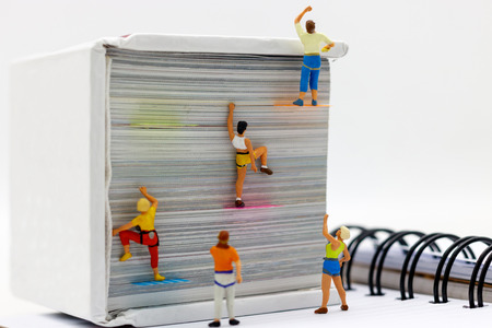 Miniature people climbing book with challenging route on cliff, Concept of the path to purpose and success. Stockfoto
