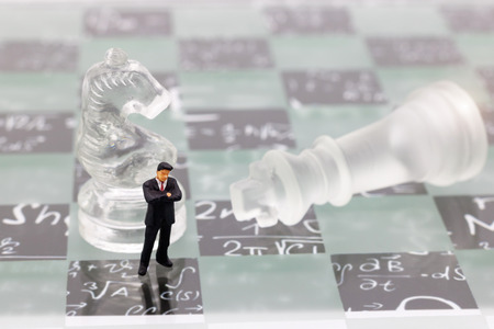 Miniature people, businessman with glass chess standing on chessboard. Concept of Strategy with thinking and intelligence challenge.