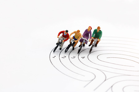 miniature people: Cyclist on the race against competitors. Imagens