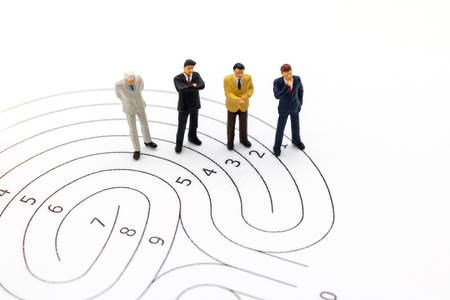 Miniature people: Businessman standing on maze and  thinking how to solve this problem. Concepts of finding a solution, problem solving and challenge.