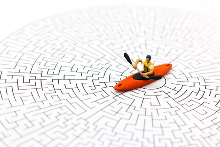 Miniature people: Canoeer rowing on center of maze and thinking how to solve this problem. Concepts of finding a solution, problem solving and challenge.