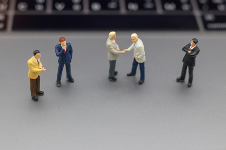 Miniature people: Businessman handshake to business success Online on laptop. Commitment, agreement, investment and partnership concept Stock Photo