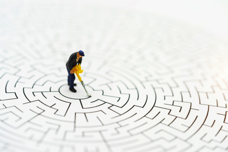 Miniature people: Worker man breaking down the walls in the maze. Concepts of problem solving, challenge and Unexpected solutions concept.