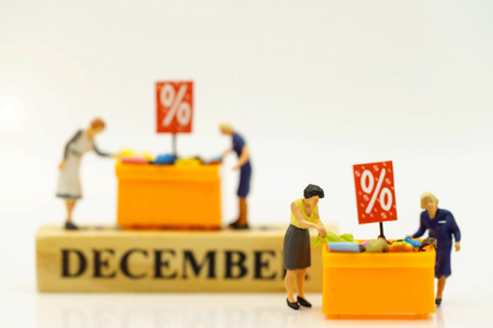 Miniatrue people: Shoppers buy goods on sale with discount tray. Tourism, shopping or business concept.