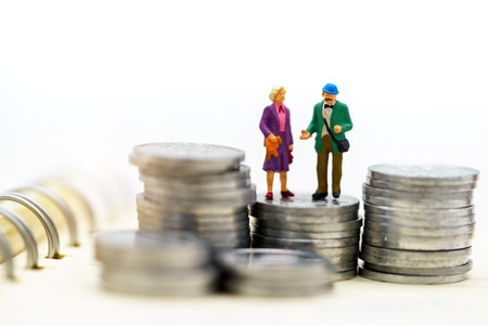 Miniature people: Happy senior couple standing on coins stack, money saving growth. Retirement, emergency plan and Financial Concept.