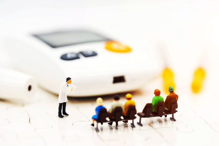 Miniature people: Doctors standing with glucose meter of diabetes  and injection needle , business and health care concept.