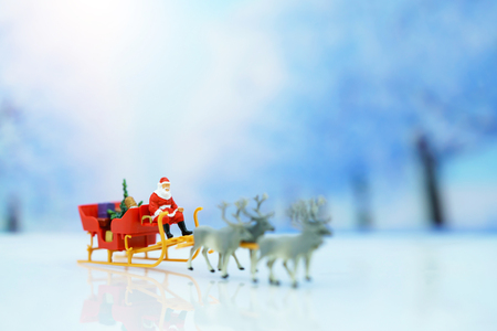 Miniature people: Santa Claus sitting Reindeer Sleigh with greeting or postal card and christmas tree. Christmas and Happy New Year concept.