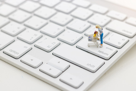 Miniatrue people: Shoppers with shopping cart standing  on keyboard. Shopping online and business concept.