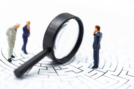 Miniature people: Businessman use magnifying glass to find the route on the maze. Concepts of finding a solution, problem solving and challenge.
