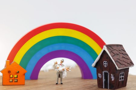Miniature people: Lover standing with house and rainbow, happy family day concept. Stok Fotoğraf