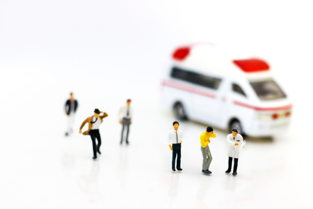 Miniature people: Doctor and patient standing with ambulance. Health care and emergency concept.