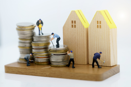 Miniature people: Workers working with tools on coins stack with wood house. Renovation and property service concept.