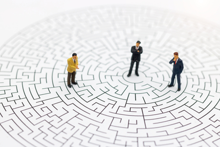 Miniature people: Businessman standing on center of maze. Concepts of finding a solution, problem solving and challenge.