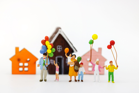 Miniature people: family and children enjoy with colorful balloons and house, happy family day concept. Stock Photo
