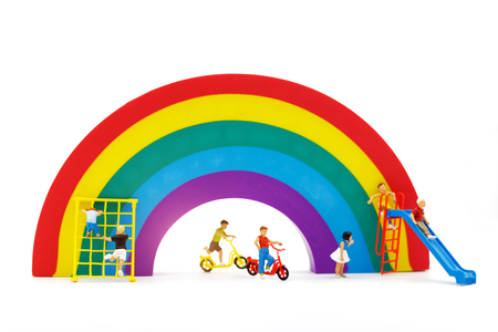 Miniature people: family and children enjoy with rainbow, happy family day concept.
