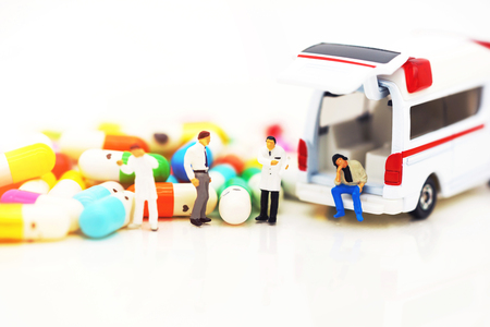 Miniature people: Doctor and patient standing with ambulance  and drugs. Health care and emergency concept.