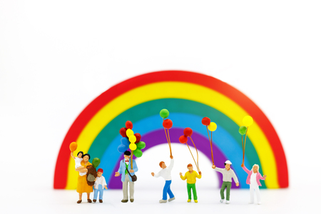 Miniature people: family and children enjoy with colorful balloons on rainbow, happy family day concept.