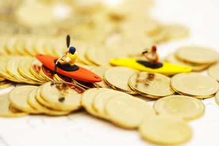 Miniature people Canoe paddle on a gold coins stack. Finance, investment and growth in business concept. Foto de archivo - 115915189