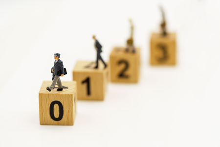 Miniature people : Businessmen standing on the wood block with sequence number. Concept of the business career growth.