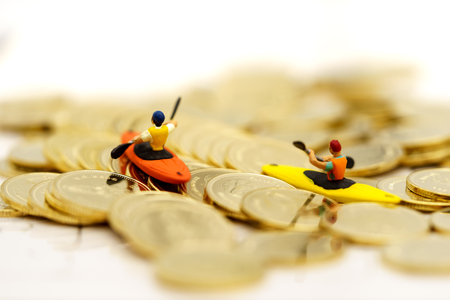Miniature people Canoe paddle on a gold coins stack. Finance, investment and growth in business concept. Foto de archivo - 115915583