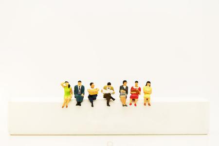 Personnes miniatures : livre de lecture d'équipe d'affaires sur la boîte en bois blanche.