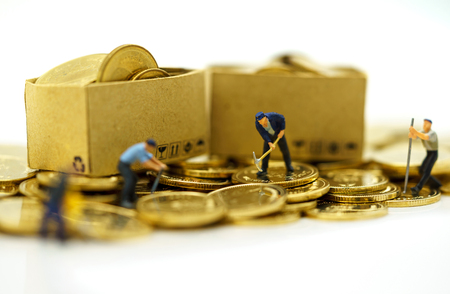 Miniature people: Workers working on golden coins with boxs. Finance, investment and growth in business concept.