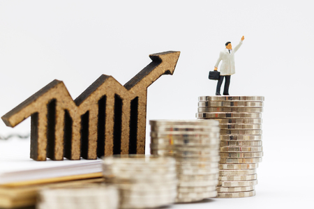 Miniature people:  Businessmen standing on coins stack with graph, Finance, investment and growth in business concept. Imagens