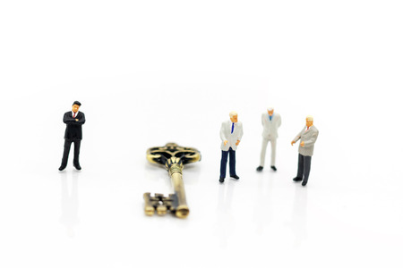 Miniature businessman handshake with unlock the keys, agreement, investment, partnership and business concept