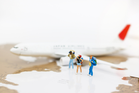Miniature people: Traveller with backpack walking on the path of tourism by airplane. Travel, explore and adventure concept Standard-Bild