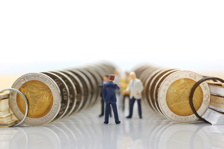 Miniature people:  Businessmen standing with coins stack, Finance, investment and growth in business concept. Foto de archivo - 118982949