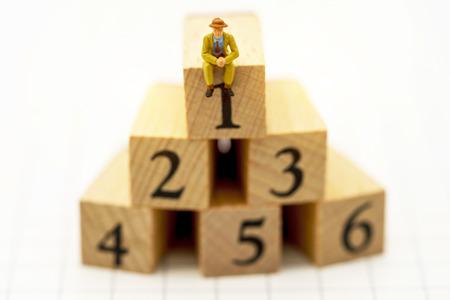 Miniaturleute: Geschäftsleute, die auf einer Holzkiste mit den Nummern 1,2,3,4,5 und 6 sitzen. Wachstum der Geschäftskarriere, Leistung, Erfolg, Sieg oder Top-Ranking-Konzept. Standard-Bild