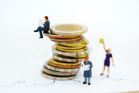 Miniature people: Business team reading book  on coins stack, education or business concept.