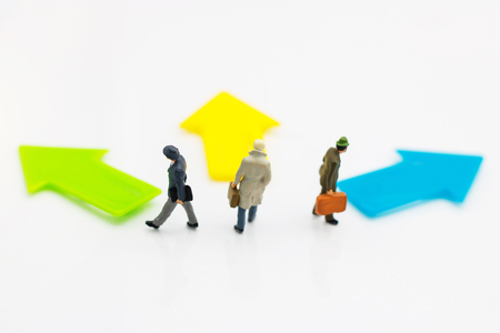 Miniature people standing whit arrow pathway choice. Concepts of problem solving, challenge and Unexpected solutions.