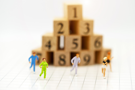 Miniature people running before wooden box number.Business career growth,  achievement, success., victory or top ranking Concept. Stock Photo
