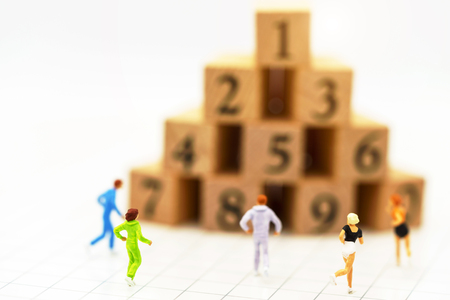 Miniature people running before wooden box number.Business career growth,  achievement, success., victory or top ranking Concept. Reklamní fotografie