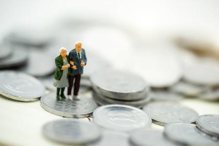 Miniaturmenschen: Glückliche alte Menschen, die auf Münzstapel stehen, Altersvorsorge, Notfallplan, Lebensversicherung und Finanzkonzept.