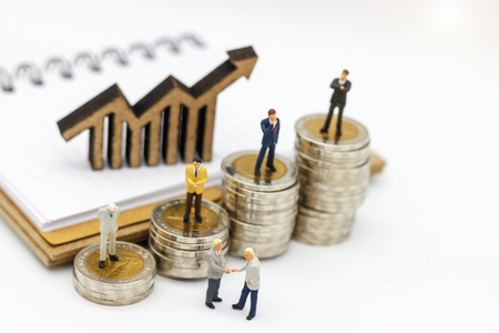 Miniature people:  Businessmen standing on coins stack with graph, Finance, investment and growth in business concept.