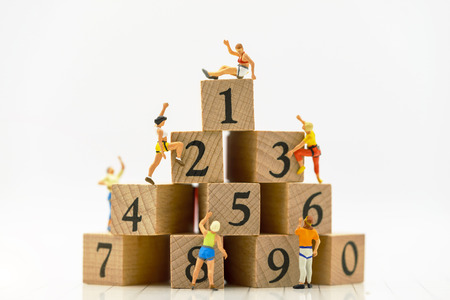 Miniature people climbing wooden box with achieving top. Achievement, success., victory or top ranking Concept.