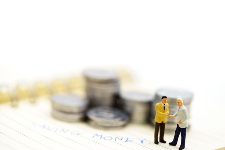 Miniature people: Businessmen handshake with coins stack, finance, investment and growth in business concept.