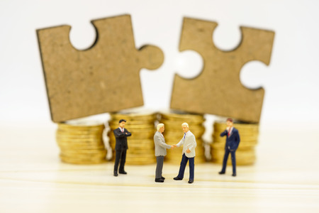 Miniature people: Businessmen handshake with jigsaw on coins stack, agreement, partnership and business concept Reklamní fotografie