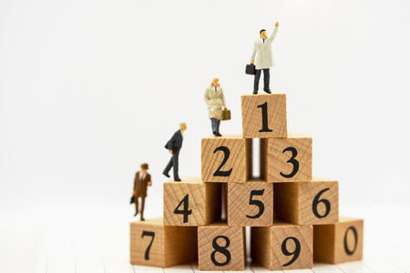 Miniature people: Business people standing on wooden box with top of ranking. Business career growth, achievement, success, victory or top ranking concept.